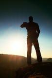 Viandante maschio sola nel paesaggio della montagna al tramonto all'orizzonte Bello panorama variopinto della montagna nella sera Fotografie Stock Libere da Diritti