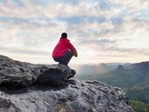 Viandante sola di F in vestiti all'aperto rosso scuro che si siedono sulla roccia Picco roccioso tagliente Immagine Stock Libera da Diritti