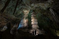 Viandanti che esplorano una caverna drammatica Fotografia Stock