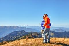 Viandanti che fanno un'escursione godendo della vista che esamina il paesaggio della montagna Fotografia Stock