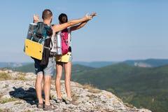 Viandanti con gli zainhi che godono della vista della valle dalla cima di una montagna. fotografie stock