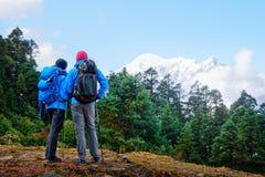 Viandanti con gli zainhi che guardano sopra la montagna durante l'aumento i Fotografia Stock