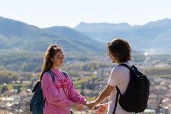 Viandanti con gli zainhi che si rilassano sopra una montagna e che godono della vista della valle fotografie stock