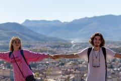 Viandanti con gli zainhi che si rilassano sopra una montagna e che godono della vista della valle immagini stock