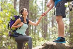 Viandanti felici che scalano sulla roccia Fotografia Stock