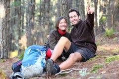 Viandanti felici delle coppie che fanno un'escursione nella foresta di autunno Fotografie Stock