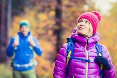 Viandanti felici delle coppie della donna e dell'uomo che camminano in legno di autunno fotografia stock libera da diritti
