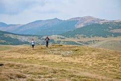 Viandanti sportive sul percorso con i pali di trekking fotografie stock