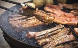 Viande épicée savoureuse de rotation étant faite cuire sur un braai ou un barbecue images stock