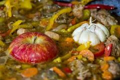 Viande avec des pommes de terre, des pommes et l'ail dans un chaudron sur le feu Photo stock