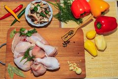 Viande brute de poulet sur un mensonge de table de cuisine, de légumes et d'accessoires de cuisine tout près image libre de droits