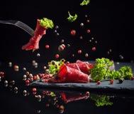Viande coupée en tranches avec des verts sur un fond noir images libres de droits