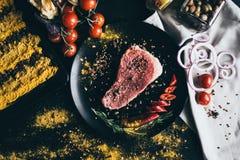 Viande crue avec des épices, des tomates-cerises, le poivre, l'oignon et des olives, se trouvant sur le fond noir et la serviette Image libre de droits