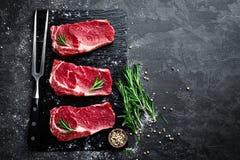 Viande crue, bifteck de boeuf sur le fond noir Photographie stock