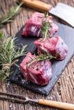 Viande crue de boeuf Bifteck cru de filet de boeuf sur une planche à découper avec du sel de poivre de romarin en d'autres positi Photos libres de droits