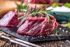 Viande crue de boeuf Bifteck cru de filet de boeuf sur une planche à découper avec du sel de poivre de romarin en d'autres positi Photos stock
