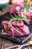 Viande crue de boeuf Bifteck cru de filet de boeuf sur une planche à découper avec du sel de poivre de romarin en d'autres positi Images libres de droits