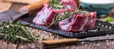 Viande crue de boeuf Bifteck cru de filet de boeuf sur une planche à découper avec du sel de poivre de romarin en d'autres positi Image stock