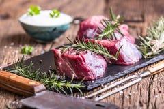 Viande crue de boeuf Bifteck cru de filet de boeuf sur une planche à découper avec du sel de poivre de romarin en d'autres positi Image libre de droits