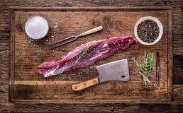 Viande crue de boeuf Bifteck cru de filet de boeuf sur une planche à découper avec du sel de poivre de romarin en d'autres positi Photo stock