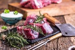 Viande crue de boeuf Bifteck cru de filet de boeuf sur une planche à découper avec du sel de poivre de romarin en d'autres positi Images stock