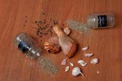 Viande crue de crevette de poulet sur un carton gris en bois, épices pour le poulet, sel, romain, basilic, ail, poivre, sauce de  photographie stock libre de droits