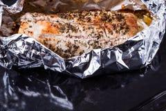 Viande cuite au four avec l'assaisonnement dans l'aluminium sur le plateau noir Image libre de droits