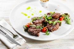 Viande délicieuse grillée de boeuf de bifteck d'un plat blanc sur un menu léger de fond Photos libres de droits