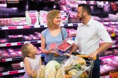 Viande de achat de famille dans le supermarché Image stock