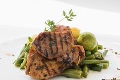 Viande de BBQ avec des légumes d'un plat blanc photographie stock
