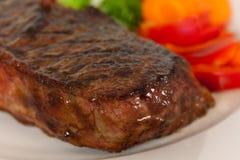 Viande de bifteck de New York sur les haricots verts, raccord en caoutchouc, poivre Photos stock