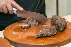 Viande de boeuf rôtie par coupes de cuisinier Le concept de la cuisson Photographie stock