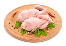 Viande de cailles sur le conseil rond D'isolement sur le fond blanc Photos stock