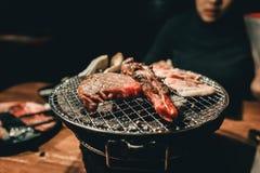 Viande de porc étroite sur un gril de charbon de bois dans le restaurant photographie stock