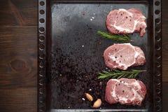 Viande de porc crue avec des épices sur le fond foncé en métal Photographie stock libre de droits