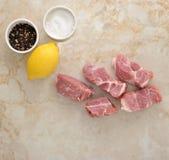 Viande de porc et sel et poivre crus coupés en tranches sur un fond de marbre Image stock