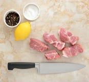 Viande de porc et sel et poivre crus coupés en tranches sur un fond de marbre Photo stock