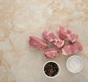 Viande de porc et sel et poivre crus coupés en tranches sur un fond de marbre Images stock
