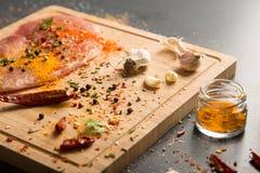 Viande de porc fraîche crue à bord avec des condiments sur le fond foncé Photo libre de droits