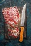 Viande de porc fumée de coppa avec le couteau de cuisine sur le fond en bois rustique Spécialité italienne traditionnelle faite à photo stock