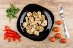 Viande de poulet frit dans le plat, les tomates, le poivre, le persil et la fourchette Photos libres de droits