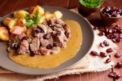 Viande de sanglier avec les pommes de terre, les champignons et les canneberges rôtis photos stock