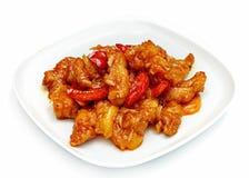 Viande en sauce aigre-doux et poivron rouge dans un plat sur un fond blanc Image libre de droits