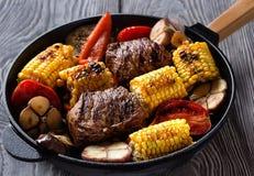 Viande et légumes frits sur une poêle de fonte Photo stock