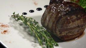 Viande et un brin de thym d'un plat blanc banque de vidéos