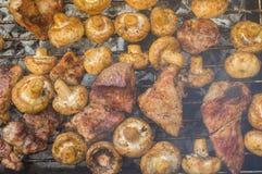 Viande faisant cuire avec des champignons de champ extérieurs sur les carbones de combustion lente photos stock