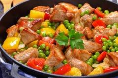 Viande frite avec les pois, oignon, paprikas Images stock