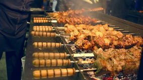 Viande grillée sur des brochettes Nourriture de rue Viande tournant sur la brochette banque de vidéos