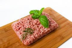 Viande hachée avec le basilic sur un panneau de découpage boisé Image stock