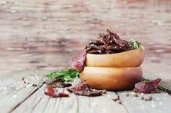 Viande lancée, vache, cerfs communs, bête sauvage ou biltong dans des cuvettes en bois sur une table rustique, foyer sélectif photographie stock libre de droits